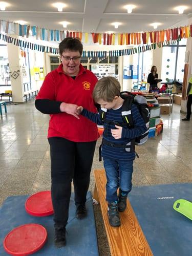 Physiotherapeutin prüft Schulranzen an Kinderrücken bei Gerblinger
